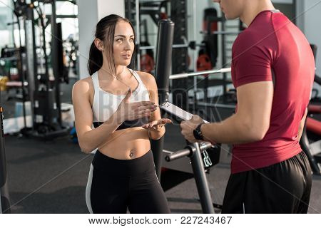 Portrait Of Young Woman Talking To Personal Fitness Coach In Modern Gym, Copy Space