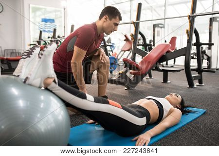 Full Length  Portrait Of Muscular Fitness Coach Helping Young Woman Doing Exercises On Mat In Modern