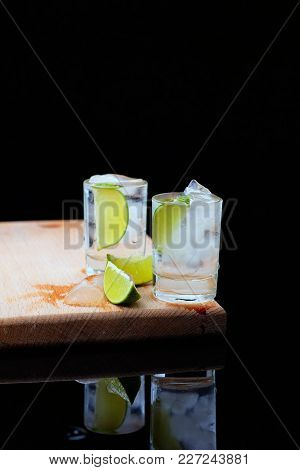 Two Shots Of Strong Alcohol On A Wooden Board, Inside Which The Ice Cubes And Lime, Cut Into Wedges.