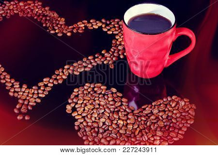 A Cup Of Coffee And Coffee Beans. Red Coffee Cup And Coffee Beans In The Shape Of Hearts On A Black