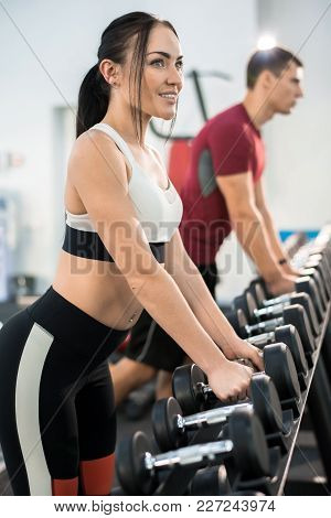Side View Portrait Of Beautiful Young Woman Picking Up Dumbbells From Equipment Rack In Modern Gym
