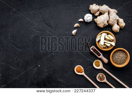Condiments, Seasoning And Spices Concept. Dry Spices In Wooden Spoons On Black Background Top View.