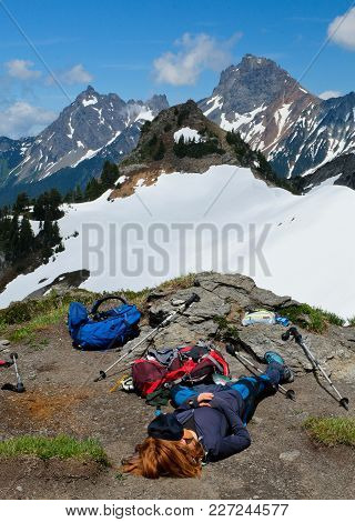 A Woman Hiker Rests On The Summit Of Yellow Aster Butte Below Canadian And American Boarder Peaks. N