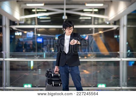 Young Asian Man Checking The Time From His Watch While Waiting For Check-in In The International Air