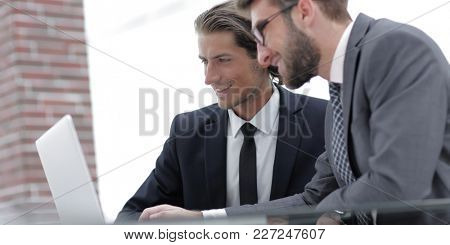 Male executives in office, looking at computer