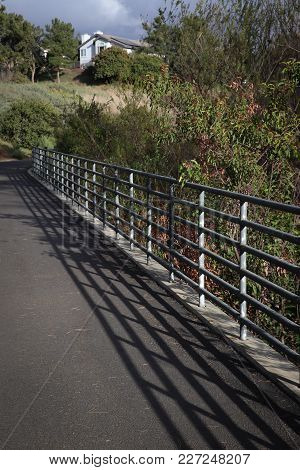 Strong Aluminum Railing Anchored In Cement Curbing Borders A Paved Trail Through Open Space In A Com