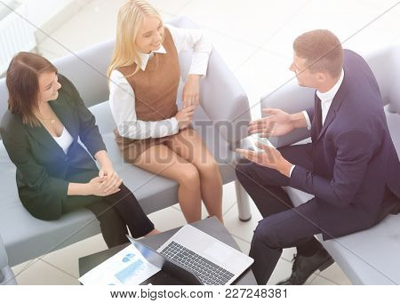 business team discussing financial documents sitting in the lobb