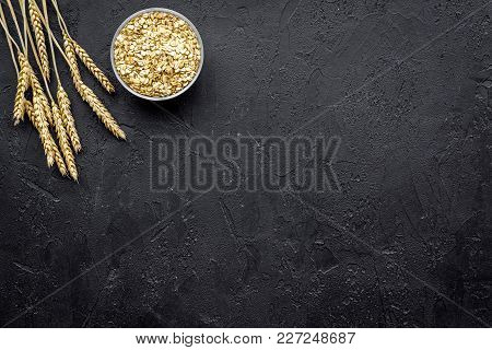 Cereals Background. Raw Oatmeal Near Sprigs Of Wheat On Black Background Top View.
