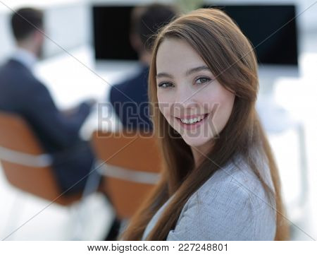 smiling female assistant in the background of the office