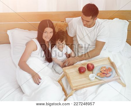 Mother, father, baby on the bed in the room