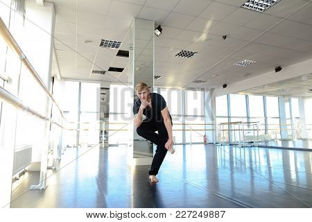 Male Dance Trainer Sitting On Twine And Tilting Trunk Forward. Boy In Good Shape Making Stretching E