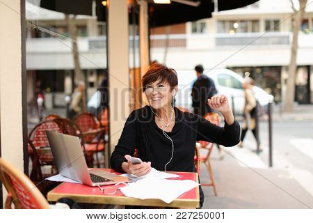Middle-aged Woman Tourist Standing Near Italian Cafe And Listen Music In Smartphone By Earphones. Pr