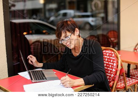 Lady Sitting In Outdoor Cafe And Have Conversation  With Sister Via Laptop. Sisters Not Communicate