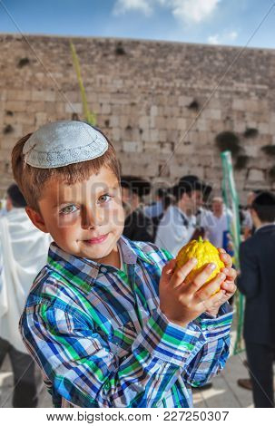 Beautiful Jewish boy with green eyes, in white skullcap, with citrus in his hand. Autumn Jewish holiday Sukkot. The greatest shrine of Judaism is the Western Wall of the Temple