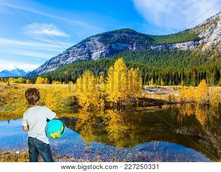 Trip to the Rocky Mountains of Canada. Boy in jeans with a globe in his hands admires the lake. Exquisite Abraham Lake with turquoise water. Concept of ecological and active tourism
