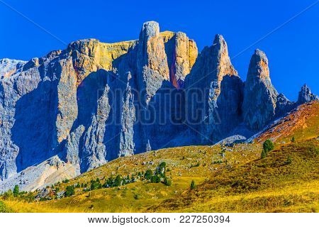 The most beautiful route in the Italian Dolomites. Southern Limestone Alps. The majestic white and gray rocks are illuminated by the morning sun. The concept of active and car tourism