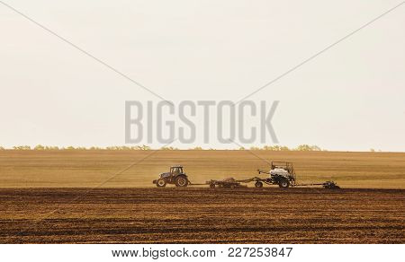 A Tractor With A Trailer Plowing Field For Sowing Of Agricultural Machinery Is Preparing For A New C