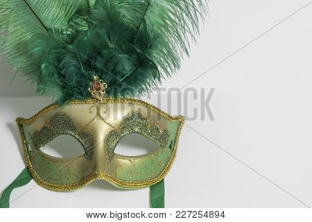Green And Gold Mardi Gras Mask With Feathers On It