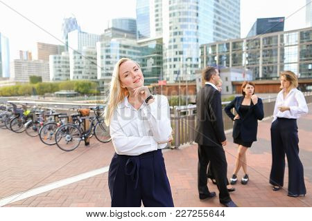 Blonde Secretary Looking At Camera And Playing With Hair Near Talking Employees Background. Concept