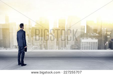 Businessman standing with his back on a roof with objects in his hand