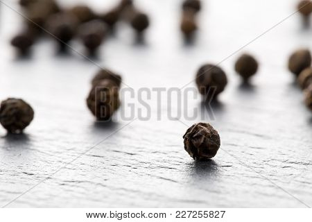 Raw, Natural, Unprocessed Black Pepper Peppercorns Macro On Dark Stone Background With Selective Foc