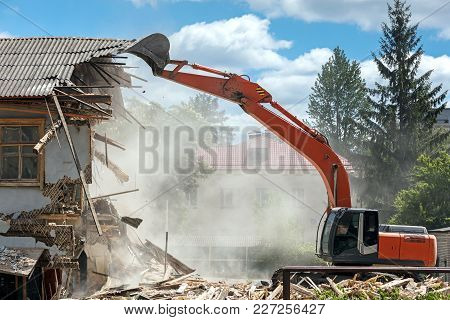 Industrial Excavator Working At The Demolition Of An Old Residential Building