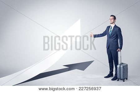 Young businessman hitchhiking with progressive arrow concept and copyspace