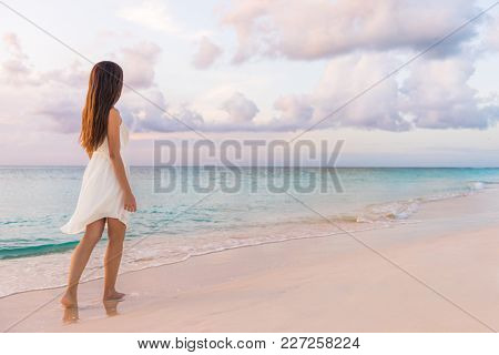 Peaceful vacation paradise woman walking on sunset beach with pastel colors sky and ocean for tranquility and serenity . Girl in white dress relaxing on luxury tropical summer getaway.