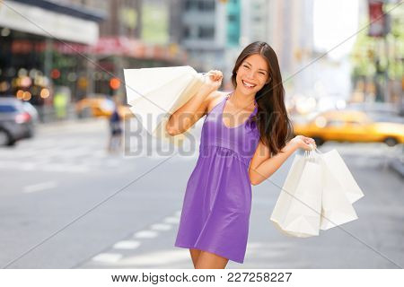 Shopper woman holding shopping bag walking in New York City having fun outside in NYC summer. Asian girl in purple pantone color fashion dress buying bag. Clothing purchase customer.