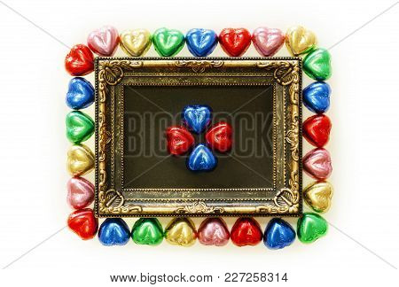 Valentines Day Background With Colorful Chocolates Heart Shape And Gold Frame From Top View. Copy Sp