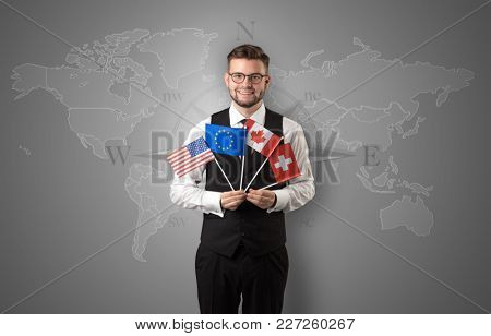 Cheerful businessman standing in front of a map with flag on his hand