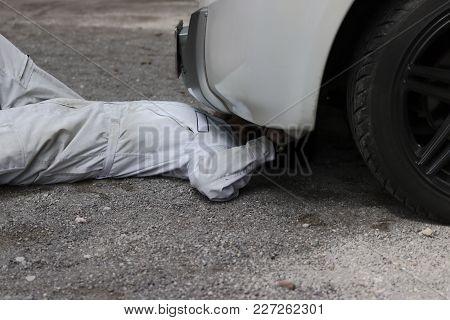 Professional Mechanic Man In White Uniform Lying Down And Repairing Under Car. Car Maintenance Conce