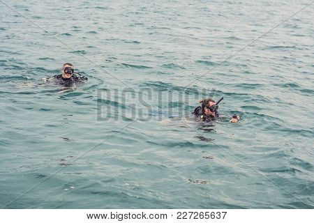 Divers On The Surface Of Water Ready To Dive.