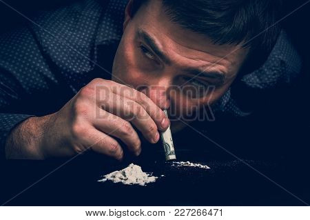 Junkie Man Snorting Cocaine Powder With Rolled Banknote On Black Background - Retro Style