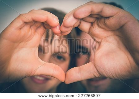 Couple Making Heart Shape With Hands And Looking Through It - Loving Couple Concept - Retro Style