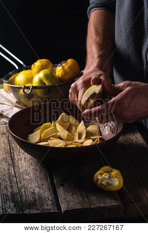 The Man Cuts The Slices With The Fruits Of Quince For Jam