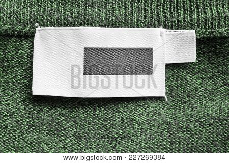 Blank Textile Clothes Label On Green Knitted Background Closeup