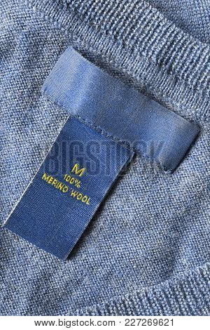 Fabric Composition Clothes Label On Blue Wool Knitted Background Closeup