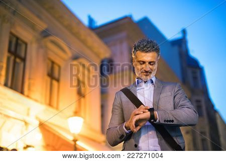 Handsome Mature Businessman With A Smartwatch In A City In The Evening, Checking The Time.