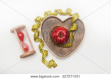Diet And Fitness Healthy Food Regime:glass Clock And Red Ripe Apple In Heart Shape Wooden Box