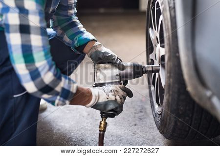 Female Mechanic Repairing A Car. An Unrecognizable Woman Working In A Garage.