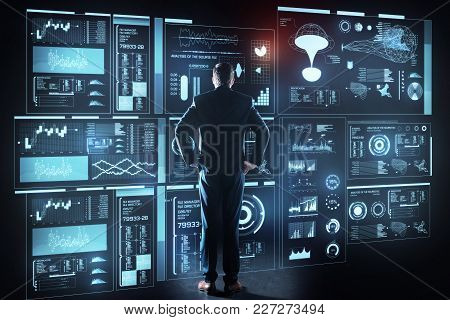Thoughtful Programmer. Calm Concentrated Experienced Programmer Standing In Front Of A Giant Futuris