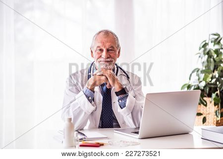Senior Male Doctor With Laptop Sitting At The Office Desk.