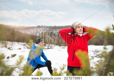 Senior Couple Jogging Outside In Winter Nature, Stretching.