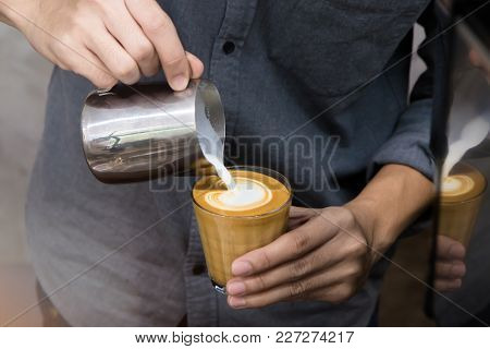 Close-up Of Male Barista Hand Holding And Pouring Hot Milk For Prepare Latte Art On Piccolo Latte Cu