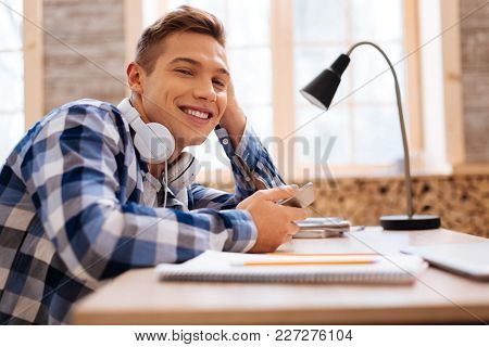 Good Day. Good-looking Alert Fair-haired Boy Smiling And Holding His Modern Phone While Sitting At T