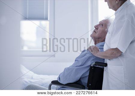 Nurse Supporting Disabled Elderly Man