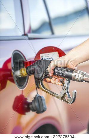 Fuel A Tank Of A Car. Hand Holding An Automotive Refueling Gun.