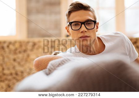 Unsmiling. Attractive Thoughtful Fair-haired Young Man Wearing Glasses And Thinking While Sitting On