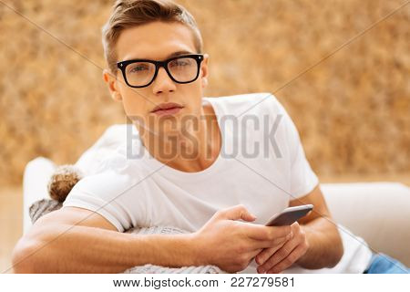 Unlucky Day. Attractive Worried Unsmiling Young Man Wearing Glasses And Holding His Phone And Feelin